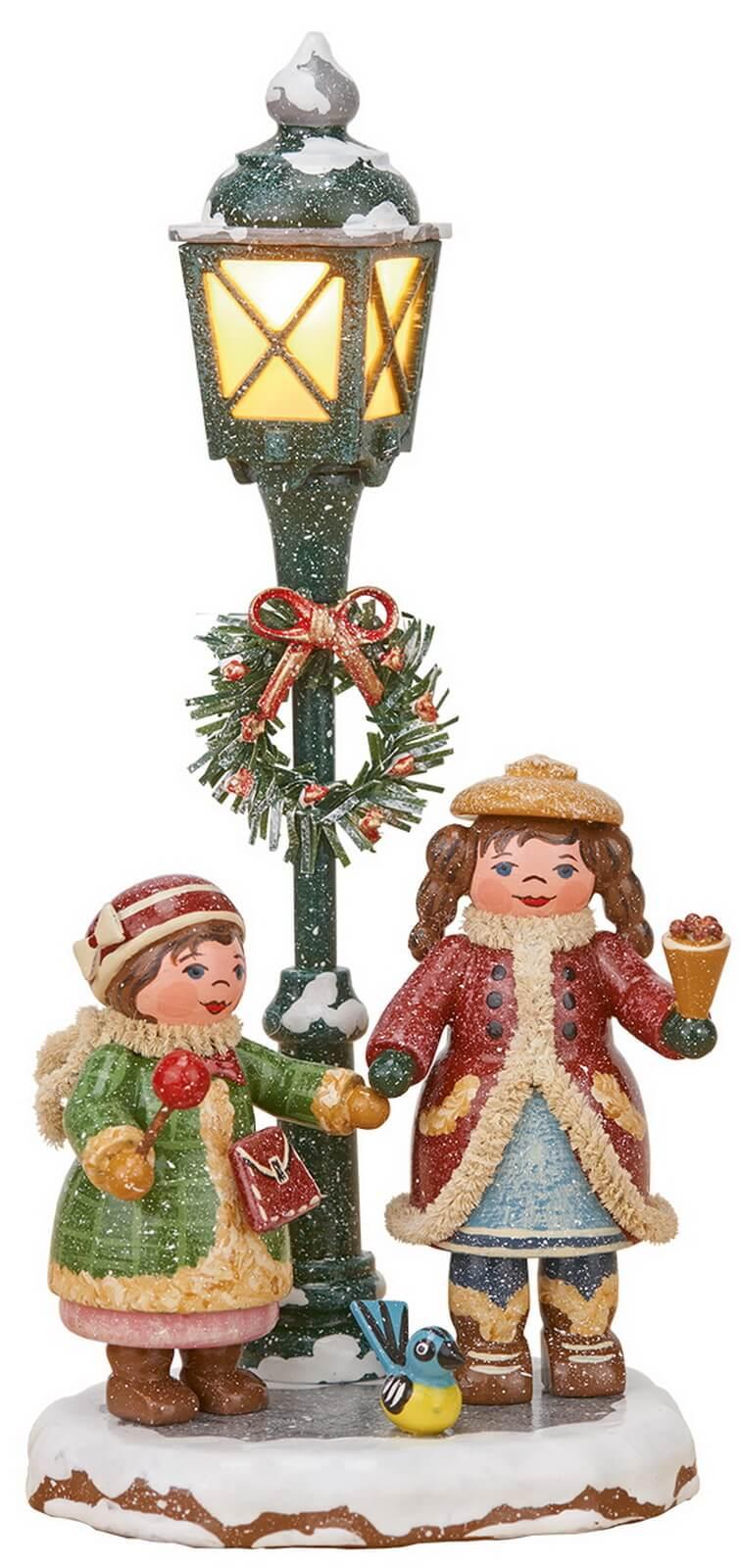 zwei strahlende Kinder an einer Laterne aus der Serie Hubrig Winterkinder