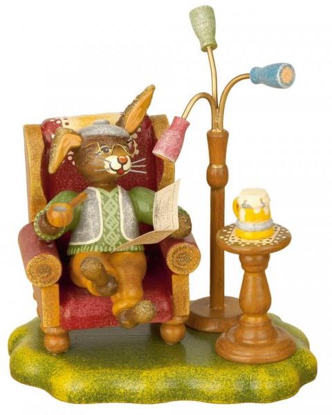 Hasenopa von Hubrig sitzend im Sessel liest Zeitung und raucht eine Pfeife