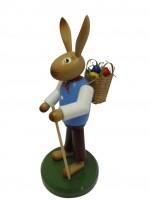 Vorschau: Osterhase mit Korb aus Buchenholz, handbemalt, Osterhase ausgerüstet mit einem Rückenkorb und Wanderstock, stehend auf einem grünen Sockel, 27 cm, …