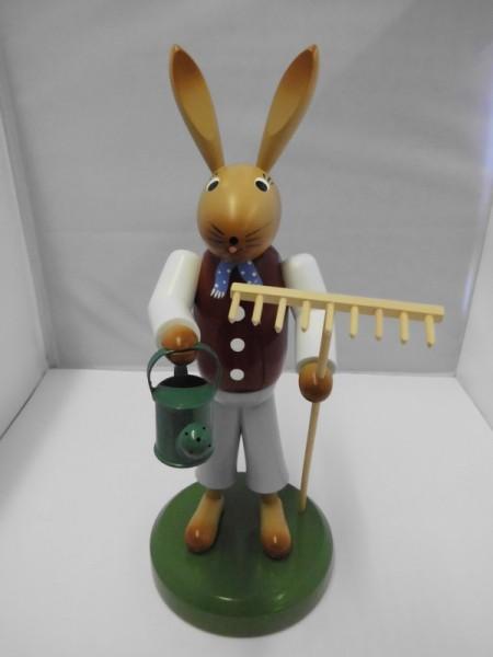 Osterhase mit Rechen bunt 27 cm hoch. In seinen Händen hält er eine Gießkanne und einen Rechen, Nestler-Seiffen.com OHG Seiffen/ Erzgebirge