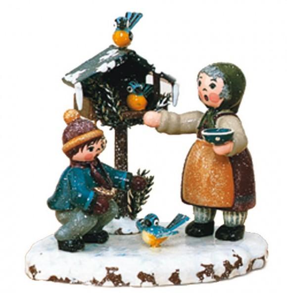 Winterkind Vogelfütterung von Hubrig Volkskunst GmbH Zschorlau/ Erzgebirge ist 9 cm groß.