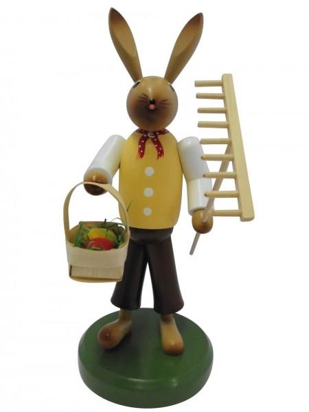 Osterhase aus Buchenholz, handbemalt, Osterhase ausgerüstet mit Rechen und einem Osterkorb, stehend auf einem grünen Sockel, 28 cm, Nestler-Seiffen.com OHG …